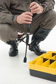stock photo of spinner  - Fisherman in grey watertight costume and black waders holding the spinner and sitting near the box for fishing baits - JPG