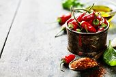 pic of pepper  - Red Hot Chili Peppers with herbs and spices over wooden background  - JPG