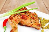 roast meat : roasted chicken legs garnished with green peas , peppers , and garlic on white plates o