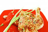 meat food : grilled quarter chicken garnished with green sprouts and red peppers on red plate isolat