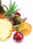 diet food - a lot of fresh raw tropical fruits include pineapple plum and mango in small basket isol