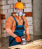 Man  in builder helmet with electric planer.