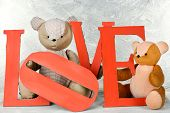 Decorative letters forming word LOVE with teddy bear on grey background