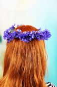 Fresh cornflower wreath on female head on light background