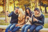 summer, holidays, vacation, happy people concept - group of friends or couples with smartphone havin