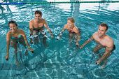 Fitness class doing aqua aerobics on exercise bikes in swimming pool at the leisure centre