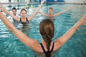 Smiling female fitness class doing aqua aerobics in swimming pool at the leisure centre