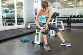 stock photo of knee  - Fit brunette sitting on bench holding injured knee at the gym - JPG