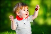 Happy Baby Have Fun In The Park On A Sunny Meadow With Cherries. Summer Vacation Concept. The Emotio