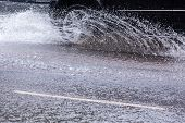 stock photo of flood  - Car crossing a flooded road during a strong rain - JPG