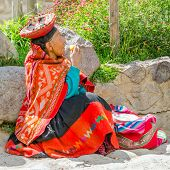 PERU, OLLANTAYTAMBO, MAY 4, 2014 - Elderly woman in traditional folk costume sits on the ground