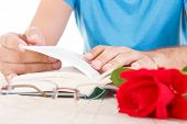 Man With His Hands Holding Open Book And Leafing Through Pages While Red Rose And Glasses Are Next T
