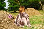 Beautiful girl sitting on haystack in field