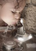 stock photo of drinking water  - Young child drinking from a water fountain - JPG
