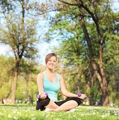 Young girl exercising with dumbbells in park seated on grass shot with tilt and shift lens