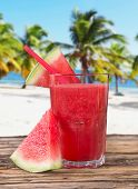 Fresh water melon juice, healthy drink on sandy beach.