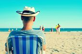 a young man with a straw hat relaxing on the beach