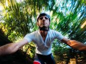 Going down in the forest; front view of a young male biker while riding fast on a single track in th