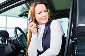 Young woman sits in new car on driver seat in a car dealership, obviously she is buying the auto, or