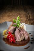 pic of duck breast  - Plate with slices of duck breast on a wooden table - JPG