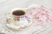 Tea in beautiful cup with peony petals