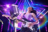 Pretty girl playing guitar against digitally generated star laser background