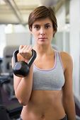 Fit brunette lifting kettlebell looking at camera at the gym