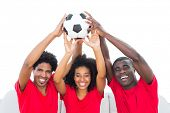 Happy football fans in red holding up ball on white background
