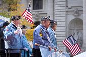 NEW YORK - NOV 11, 2014: US vets wave American Flags as they stand on a parade float in the 2014 America's Parade held on Veterans Day in New York City on November 11, 2014.