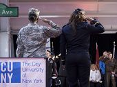 NEW YORK - NOV 11, 2014: Two female US veterans salute from the CUNY float as it passes the VIP stage during the 2014 America's Parade held on Veterans Day in New York City on November 11, 2014.