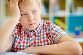 Adorable pensive schoolboy sitting at lesson