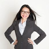 Confident young Asian business woman smiling at camera, standing on plain background.