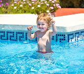 smiling  baby girl swims  in the pool in  summer