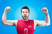 American volleyball player celebrates on blue background