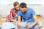 repair, building, renovation, technology and people concept - smiling couple with blueprint looking at tablet pc at home
