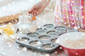 cooking, baking, food and home concept - close up of woman hand filling muffins molds with dough