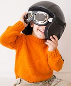 Little cute playful baby kid with pilot hat and goggles ready for airplane flying