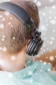 technology, music, leisure and people concept - close up of man in headphones at home from back