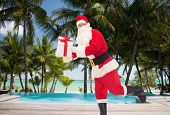 christmas, holidays, travel and people concept - man in costume of santa claus running with gift box over tropical beach and swimming pool background