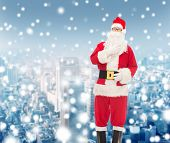 christmas, holidays and people concept - man in costume of santa claus over snowy city background