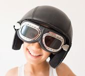 Little cute playful kid with pilot hat and goggles ready for airplane flying