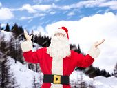 christmas, holidays and people concept - man in costume of santa claus with raised hands over snowy mountains background
