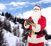 christmas, holidays, technology and people concept - man in costume of santa claus with tablet pc computer over snowy mountains background
