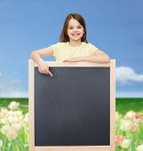 people, advertisement and education concept - happy little girl pointing finger to blackboard