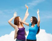 happiness, friendship and people concept - smiling teenage girls having fun over blue sky and cloud background
