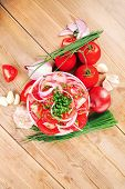 vegetable salad : fresh tomato salad in white bowl with bundle of chives , tomatoes on twig , onion, and garlic over wooden table