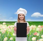 cooking, childhood, advertisement and people concept - smiling little chef girl, cook or baker with blank black paper over blue sky and field of flowers background