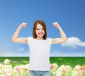 advertising, childhood, nature, gesture and people concept - smiling girl in white t-shirt with raised arms over flower field background
