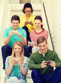 education, school and technology concept - smiling students with smartphone texting at school