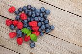 Blueberries and raspberries with mint leaf on wooden table with copy space